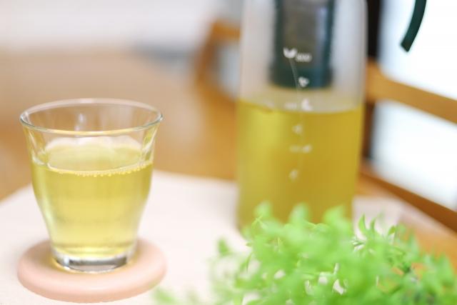 グラスに注がれた緑茶とボトル