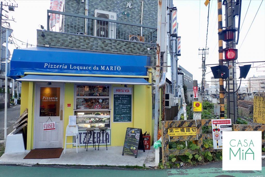 踏切の横にある青い屋根のピザ屋