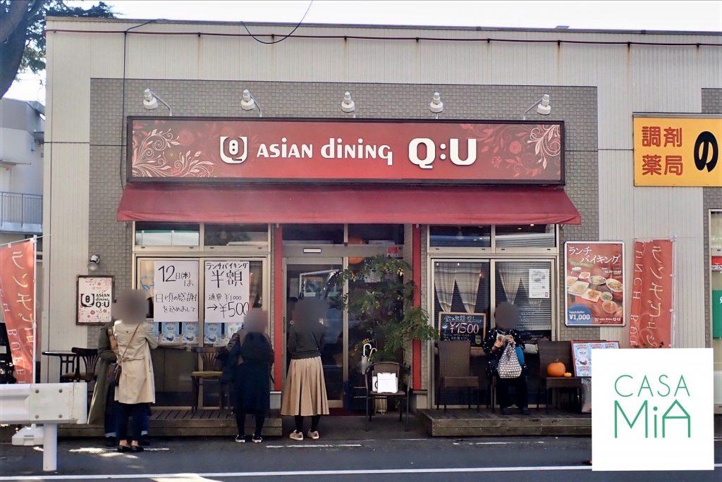 赤い建物のアジアン料理レストランとその前に並ぶたくさんのお客さん